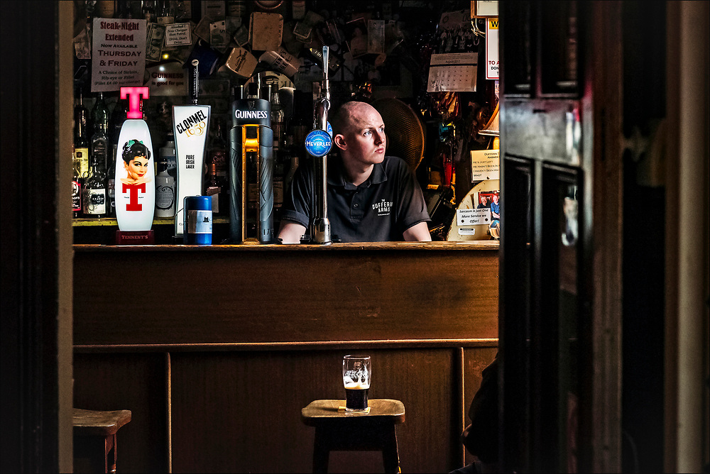 The bartender at the Dufferin Arms pub in Killyleagh in Northern Ireland presides over an old boozer that retains its early 19th century layout with a bar and tiny snugs for privacy. © Steve Raymer / National Geographic Creative