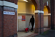 A voter walks his dog away from the church of St. Saviours in the south London borough of Lambeth, serving as a polling station for the UKs General Election 2 weeks before Christmas, on 12th December 2019, in London, England.