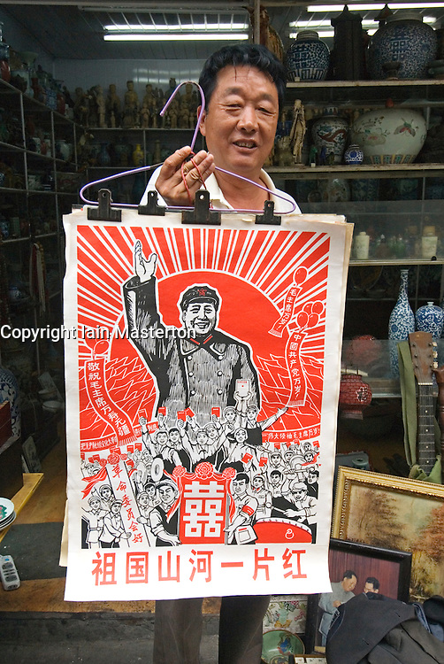 Shopkeeper holding antique revolutionary poster with Chairman Mao at Dongtai Antique Market in Shangai China