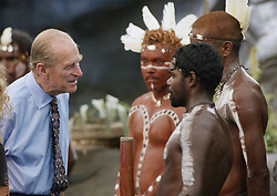 "The Duke of Edinburgh talks to Aboriginal performers after watching a culture show at Tjapukai Aboriginal Culture Park, Cairns, Queensland, Australia. The Duke surprised the aborigines when he asked them ""Do you still throw spears at each other?"""