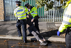 © Licensed to London News Pictures. 04/10/2021. London, UK. An arrested activist from Insulate Britain is dragged to the side of the road by police at the entrance to the Blackwall tunnel after the group blocked the tunnel earlier this morning. Insulate Britain have successfully blocked various roads around the capital over a number of weeks, resulting in a court injunction banning them from going near the M25 motorway.  Photo credit: George Cracknell Wright/LNP