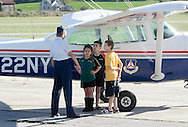 Montgomery, New York - A female member of the Civil Air Patrol's Cadet Program shows a girl and two boys a Civil Air Patrol airplane  at Orange County Airport on Oct. 2, 2010.