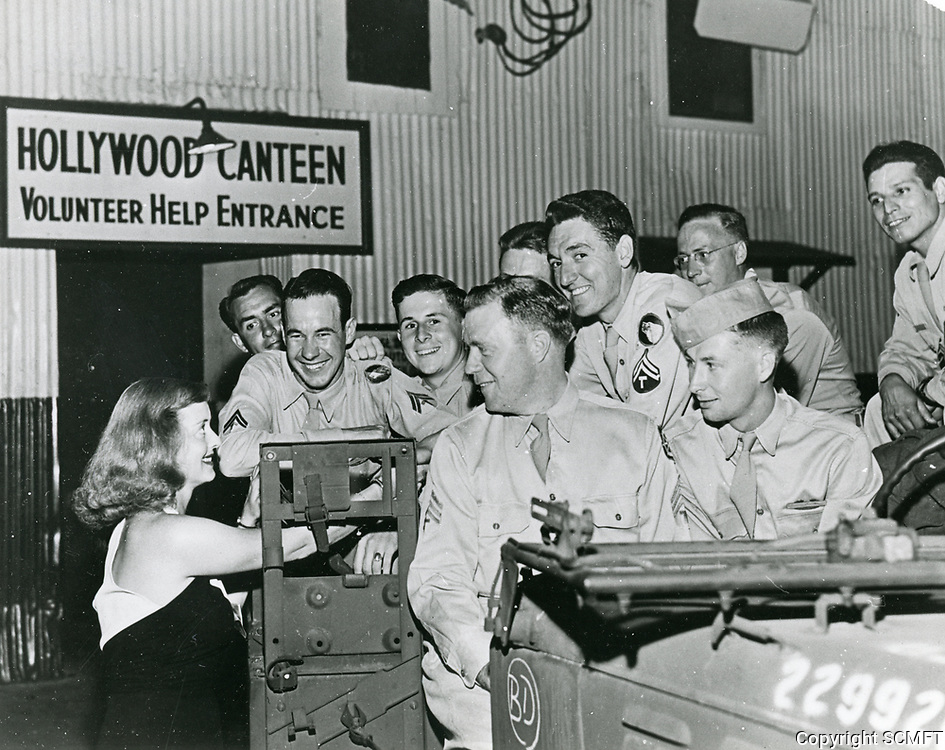 1943 Bette Davis greets a group of servicemen at the Hollywood Canteen's volunteer entrance