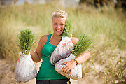The daughter of a sea oats farmer helps her dad out during the summer by carrying plants out to the beach in North Carolina