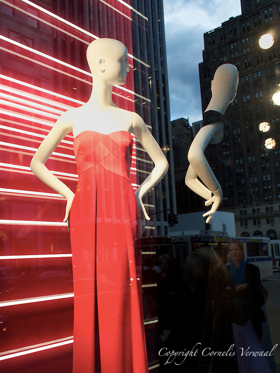 One of the mannequins seems to be stepping out of her window to check out the scene on Fifth Avenue.<br /> Georgio Armani display at Bergdorf Goodman on Fifth Avenue and 59th street.