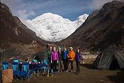 Our base camp at Jomolhari Base Camp – Left to right: Mark & Kelly Shager, Bob Holmes, Andrea Johnson, Robert 'Skp' Sandber, Amanda Mason. Mani wall with prayer flags & old fortress shadowed by the massive 24,000 foot Himalayan peak