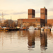 The City Hall and harbour of Olso, Norway. Located in the Pipervika district, the building was completed in 1950 and was designed by Arnstein Arneberg and Magnus Poulsson. The Nobel Peace Prize ceremony takes place here every year on December 10.<br /> <br /> + ART PRINTS +<br /> To order prints or cards of this image, visit:<br /> http://greg-stechishin.artistwebsites.com/featured/oslo-harbour-greg-stechishin.html
