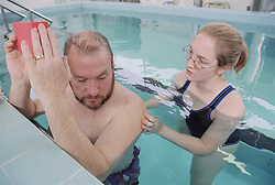 Physiotherapist working with a class of upper limb patients in hydrotherapy pool,