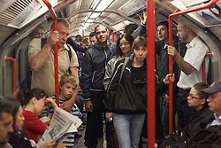 © licensed to London News Pictures. London, UK 31/07/2012. People traveling on a crowded Central Line train. The line operated with severe delays and temporarily lost its connection to Stratford (Olympic Park) on 31/07/12. Photo credit: Tolga Akmen/LNP