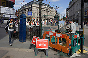 "An artist is incongruously enclosed in roadworks barriers at the busy junction of Piccadilly Circus in London's West End. Painting with an easel and applying careful brush strokes amid the noise and chaos of this busy traffic junction in the capital. A young man walks past barely noticing the artist as he strides through the heart of London's west end. But on the youth's t-shirt is a modern interpretation (wearing glasses and apparently spitting liquid into a cup) of Hans Memling's ""Portrait of a Man with a Coin of the Emperor Nero (Bernardo Bembo)"" German-born artist Jan van Mimnelinghe (Hans Memling, c. 1435-94) was well known all over Europe. During his lifetime, he painted commissions not only for the Burgundian Dukes, but also for patrons in Germany, Austria, Venice, Florence and London."