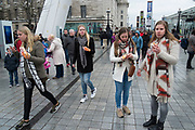 Four girls each eating a large hotdog on the Southbank, London, United Kingdom. The South Bank is a significant arts and entertainment district, and home to an endless list of activities for Londoners, visitors and tourists alike. (photo by Mike Kemp/In Pictures via Getty Images)