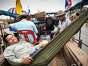21 FEBRUARY 2014 - KHLONG CHIK, PHRA NAKHON SI AYUTTHAYA, THAILAND:  A farmer relaxes in a hammock strung in a wagon. About 10,000 Thai rice farmers, traveling in nearly 1,000 tractors and farm vehicles, blocked Highway 32 near Bang Pa In in Phra Nakhon Si Ayutthaya province. The farmers were traveling to the airport in Bangkok to protest against the government because they haven't been paid for rice the government bought from them last year. The farmers turned around and went home after they met with government officials who promised to pay the farmers next week. This is the latest blow to the government of Yingluck Shinawatra which is confronting protests led by anti-government groups, legal challenges from the anti-corruption commission and expanding protests from farmers who haven't been paid for rice the government bought.   PHOTO BY JACK KURTZ