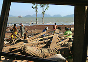 Koh Lanta, Thailand--Villagers clean up the debris left by the Tsunami which destroyed many of their homes in the village of Hua Laem on Koh Lanta Island in Southern Thailand.  Almost everyone in the village got involved in the clean-up, from young children to men and women in their 70s.  In the foreground is a window frame ripped out of a house by the powerful waves. 01/24/05 © Julia Cumes / The Image Works