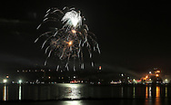 Beacon, New York -  Independence Day fireworks explode in the sky over Newburgh and reflected in the Hudson River as seen from a waterfront park on July 4, 2010.