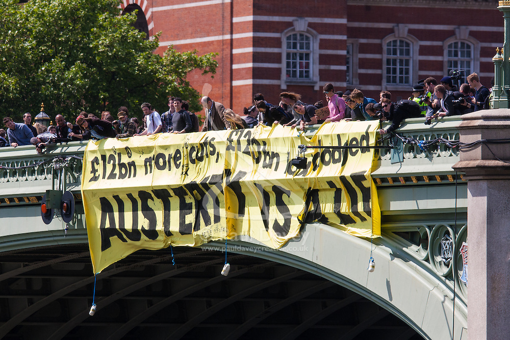 """ter, London, May 30th 2015. Anti-austerity campaigners bring traffic on Westminster Bridge as they paint and hang a banner off the bridge highlighting an alleged £120 billion owed in taxes as compared to the proposed £12 billion cuts to welfare. PICTURED: The banner proclaiming """"Austerity is a lie"""" hangs off Westminster Bridge, facing Parliament."""
