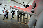 A couple look at a nude sculpture of a man on display at a gallery in Dashanzi art district in Beijing, China May 4, 2007.
