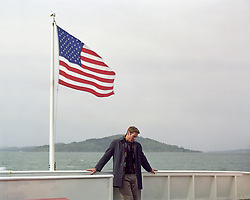 lone man on a ferry boat in San Francisco standing near the American Flag blowing in the wind