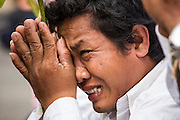 """01 FEBRUARY 2013 - PHNOM PENH, CAMBODIA: A man cries in grief as the funeral procession of former Cambodian King Norodom Sihanouk passes him in Phnom Penh. Norodom Sihanouk (31 October 1922- 15 October 2012) was the King of Cambodia from 1941 to 1955 and again from 1993 to 2004. He was the effective ruler of Cambodia from 1953 to 1970. After his second abdication in 2004, he was given the honorific of """"The King-Father of Cambodia."""" Sihanouk died in Beijing, China, where he was receiving medical care, on Oct. 15, 2012. His cremation is will be on Feb. 4, 2013. Over a million people are expected to attend the service.    PHOTO BY JACK KURTZ"""