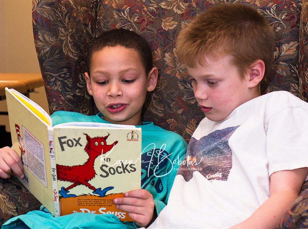 """Nehemiah and Josiah find a comfy chair and red """"Fox in Socks"""" by Dr. Seuss at the Gilford Library during Read Across America on Wednesday afternoon.  (Karen Bobotas/for the Laconia Daily Sun)"""