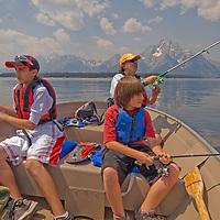 Mark, Jesse and Ross Goldblum fish from motor boat on Jackson Lake, Grand Teton National Park, Wyoming.