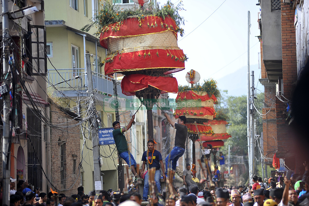 October 17, 2016 - Kathmandu, NP, Nepal - Locals carry as well as rotates top part of a chariot of Lord Narayan across the streets of Hadigaun during Lord Narayan jatra festival in Hadigaun, Kathmandu, Nepal on Monday, October 17, 2016. Once in a every year right after Dashain Festival this festival celebrates. The Narayan Jatra Festival of Hadigaun is a unique Festival in the capital involving three circular bamboo structures, above which an idol of the Lord Narayan in placed, and then rotated by two people standing below. (Credit Image: © Narayan Maharjan/NurPhoto via ZUMA Press)