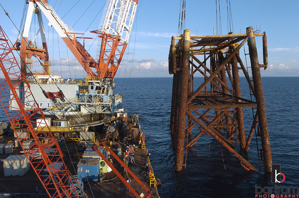 KEVIN BARTRAM/The Daily News.The top half of an abandoned offshore platform is lifted from about 200 feet of water 100 miles south of Galveston on Tuesday, June 28, 2005. A crane aboard the derrick barge Kallop lifted the El Paso Corporation before setting it on the bottom of the Gulf of Mexico to form an artificial reef. Workers cut the legs of the platform about 90 feet below the surface.