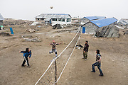 Young Nepali trekking guides and porters play a game of volleyball on the court at Annapurna Base Camp (4130m), Himalaya Mountains, Nepal.