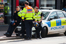 The English Defence League (EDL) return to Sheffield to lay flowers at Sheffield War Memorial . resulting in a police operationlasting over 5 hours involving Officers from Wales, South Yorkshire, Greater Manchester, West Yorkshire, Lancashire and Mersyside Police forces. Police officers take a breather during a lul in the operation <br /> 8 June 2013<br /> Image © Paul David Drabble<br /> www.pauldaviddrabble.co.uk