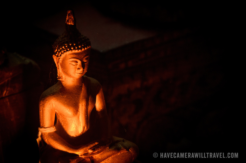 Candle light dimly illuminates a small Buddha statue at Wat Mai Suwannaphumaham.  Wat Mai, as it is often known, is a Buddhist temple in Luang Prabang, Laos, located near the Royal Palace Museum. It was built in the 18th century and is one of the most richly decorated Wats in Luang Prabang.