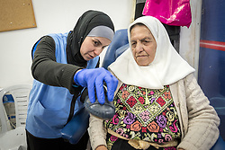 26 February 2020, Abu Dis, Palestine: Nurse Najwa Hawamdeh administers a foot exam as 87-year-old Diabetes patient Hamama Jaffal from Abu Dis visits the Augusta Victoria Hospital's Mobile Diabetes Clinic. Here, comparing the size of Jaffal's foot vis-a-vis her shoe to make sure the shoe is wide enough, as Diabetes patients often develop sensitive feet. In an effort to make Diabetes services more accessible to people in the West Bank, the Augusta Victoria Hospital offers a Mobile Diabetes Clinic, which moves around to various locations in the West Bank, offering screening and routine testing for Diabietes and the symptoms it causes.
