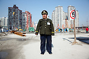 "A security guard poses for a picture at a construction site in Shanghai, China on 22 December, 2009. China has tightened land-sale regulations for developers in its latest attempt to take some of the steam out of the potentially overheating property market, this followed a recent vow from Beijing last week to curb what it calls an ""overly fast"" rise in property prices by boosting the supply of cheap public housing and redeveloping slum areas.."