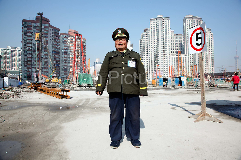 """A security guard poses for a picture at a construction site in Shanghai, China on 22 December, 2009. China has tightened land-sale regulations for developers in its latest attempt to take some of the steam out of the potentially overheating property market, this followed a recent vow from Beijing last week to curb what it calls an """"overly fast"""" rise in property prices by boosting the supply of cheap public housing and redeveloping slum areas.."""