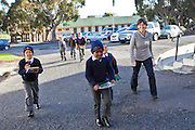 African school children walk across the school car park with their reading books accompanied by a female teacher in Zonnebloem School, Cape Town, South Africa.  They are attending an extra reading session provided by Shine Centre which is a charity that aims to address the high illiteracy rate in South Africa by improving literacy levels among children in schools and disadvantaged communities.