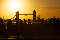© Licensed to London News Pictures. 10/10/2014. London, UK. Commuters walk over London Bridge as an orange sunrise is seen behind over Tower Bridge on the River Thames with clear sky and fine weather this morning. Photo credit : Vickie Flores/LNP