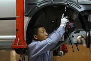 A production line worker builds a Volkswagen Jetta, on the assembley line at the China First Auto Works (FAW) plant in Changchun, China May 25, 2004. First Automotive Works (FAW), China's largest vehicle maker and partner of Volkswagen, is interested in listing abroad within the next five years.