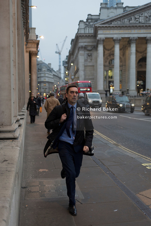 A commuter in a hurry, runs past the pillars of the Bank of England, on 9th February 2017, in the City of London, England.
