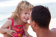 A happy moment between a father and his daughter on the beach in Hawaii