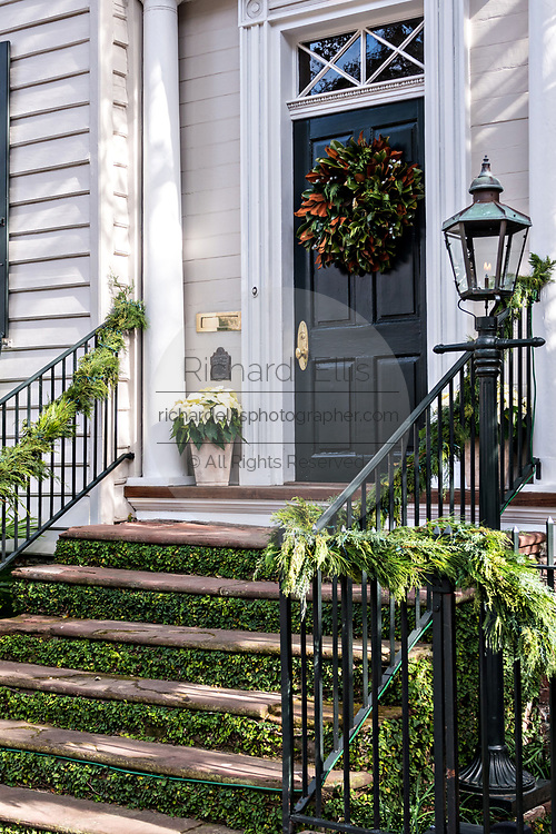 A magnolia Christmas wreath decorates a wooden door on a historic home at Legare Street in Charleston, SC.