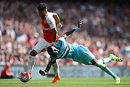 Alex Oxlade-Chamberlain of Arsenal runs past  Cheikhou Kouyate of West Ham United as he trips over. Barclays Premier League, Arsenal v West Ham Utd at the Emirates Stadium in London on Sunday 9th August 2015.<br /> pic by John Patrick Fletcher, Andrew Orchard sports photography.