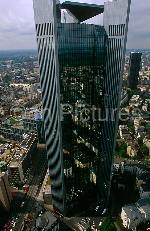 A high-rise office tower that dominates an otherwise flat cityscape in Frankfurt's financial district. With the rest of the German city spreading out into the distance, this scyscraper rises into the sky providing jobs for the administrative and financial private sector.
