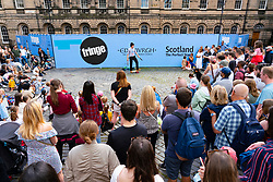 Edinburgh, Scotland, UK. 17th August  2021.  Large crowd watches a performance in West Parliament Square in the Old Town by a street performer during Edinburgh Festival Fringe 2021. Iain Masterton/Alamy Live news.