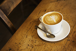 May 11, 2017 - Close up high angle view of a cup of cappuccino on a rustic wooden table, heart shape in milk foam. (Credit Image: © Mint Images via ZUMA Wire)