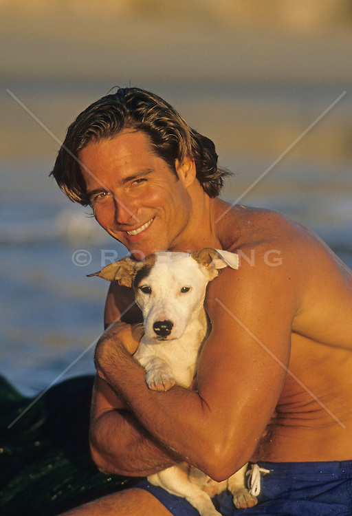 good looking man hugging a Jack Russell dog at the beach