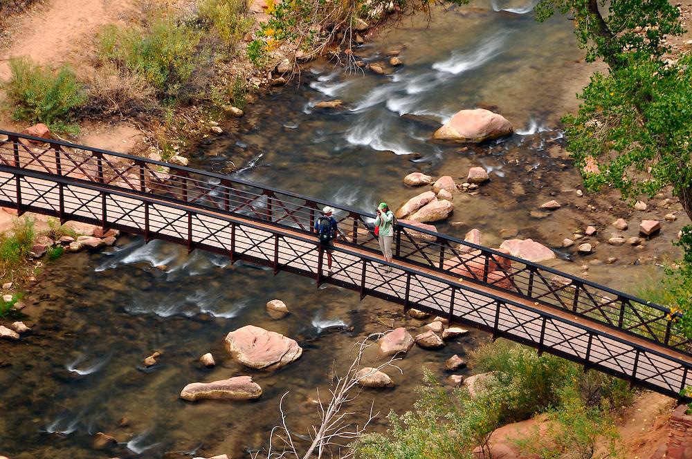 Hikers on footbridge over the Virgin River, Zion Canyon, Utah.