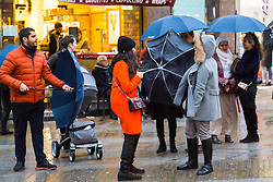 London, December 31 2017. The umbrellas come out as a downpour begins in London's west end ahead of the New Year's Eve fireworks at midnight. PICTURED: A woman's umbrella is turned inside out in Leicester Square as a gust of wind heralds the rain.  © SWNS