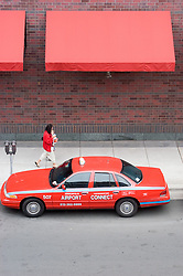 A woman dressed in red walks past a red taxi under a red awning