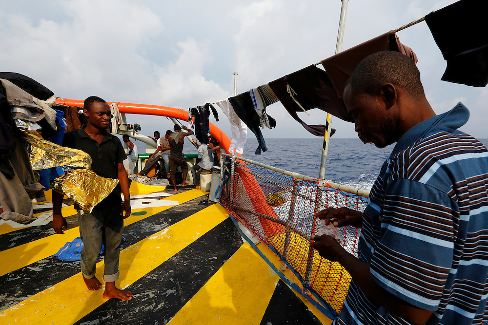 Migrants stand at the stern of the Medecins san Frontiere (MSF) rescue ship Bourbon Argos somewhere between Libya and Sicily August 8, 2015.  Some 241 mostly West African migrants on the ship are expected to arrive on the Italian island of Sicily on Sunday morning, according to MSF.<br /> REUTERS/Darrin Zammit Lupi <br /> MALTA OUT. NO COMMERCIAL OR EDITORIAL SALES IN MALTA