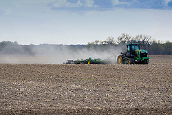 A large agricultural farm tractor pulls a piece of tilling equipment called a disc to prepare the soil for planting.