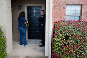 (L to R) Nekia Tillotson and Alan Bull of the Dallas Police Department go door to door as a part of the new 10/70/20 program at The Lodge at Timberglen apartments in Dallas on Saturday, March 30, 2013. (Cooper Neill/The Dallas Morning News)