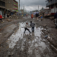 Girls in wellington boots dance in a puddle in the street in Mukuru Kwa Njenga, Nairobi, Kenya.